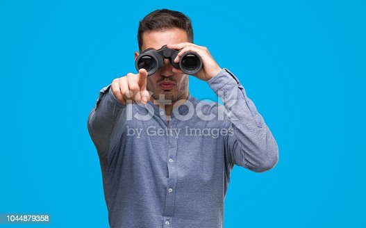 Handsome young man looking through binoculars pointing with finger to the camera and to you, hand sign, positive and confident gesture from the front