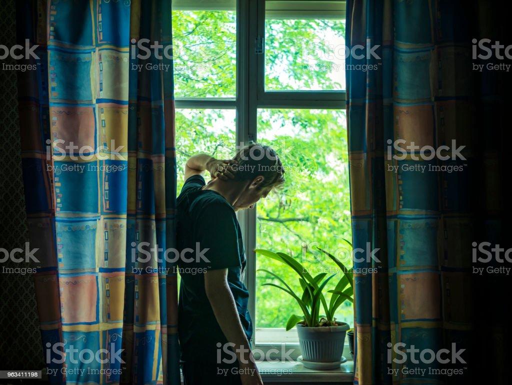 beau jeune homme, regardant par la fenêtre dans la rue un jour d'été - Photo de Adulte libre de droits