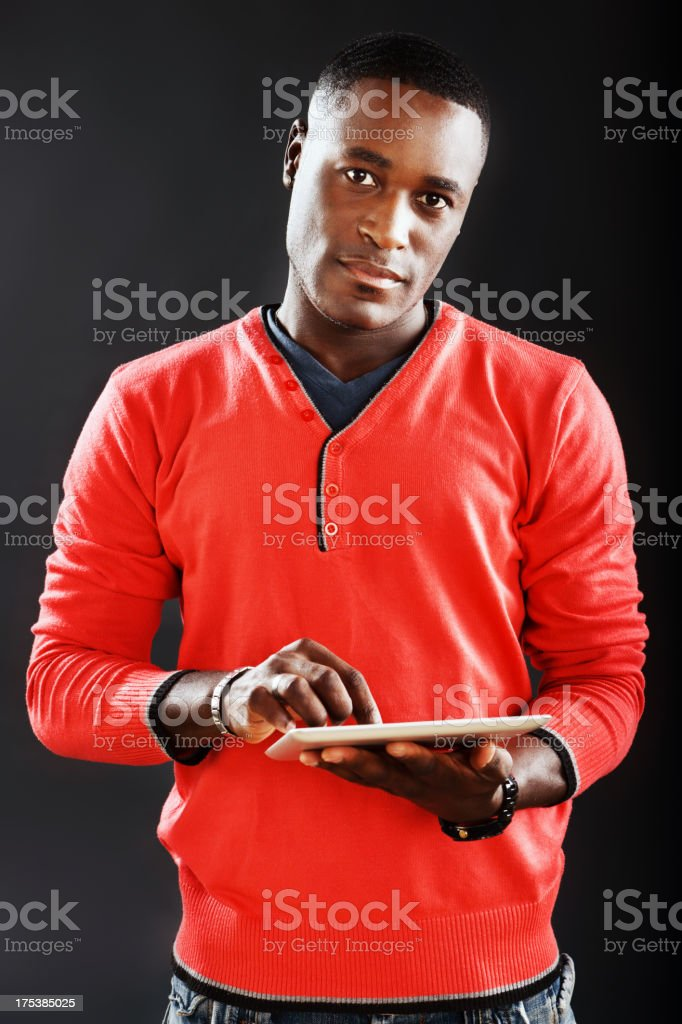 Handsome young man looks up from digital tablet stock photo