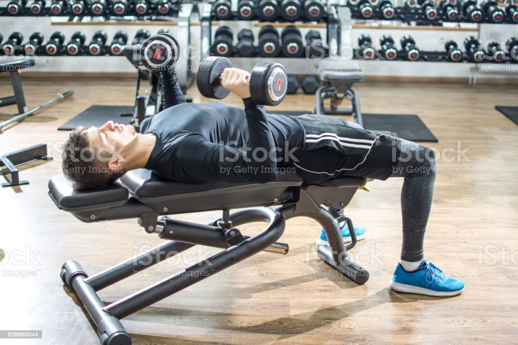 Handsome Young Man Lying On Exercise Bench And Lifting Dumbbells At Gym Stock Photo Download Image Now