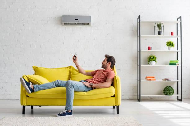 stattliche junge Mann liegt auf gelbem Sofa unter Klimaanlage und halten Fernbedienung – Foto