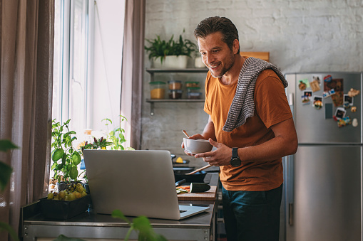 Handsome young happy Caucasian man holding a bowl, and making a meal while watching a cooking tutorial on a laptop on a kitchen counter.