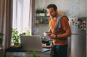 istock Handsome Young Man Making a Meal while Watching a Cooking Tutorial in a Kitchen 1297322141