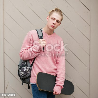 846124694 istock photo Handsome young man model with a hairstyle in a pink fashion sweater with a backpack and skateboard 846126858