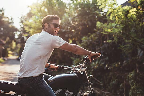 handsome young man on motorcycle - motorrad männer stock-fotos und bilder
