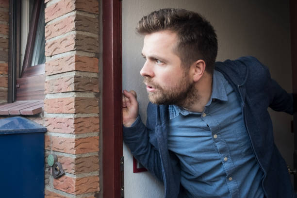 Handsome young man opening door looking on what his neighbor is doing. stock photo