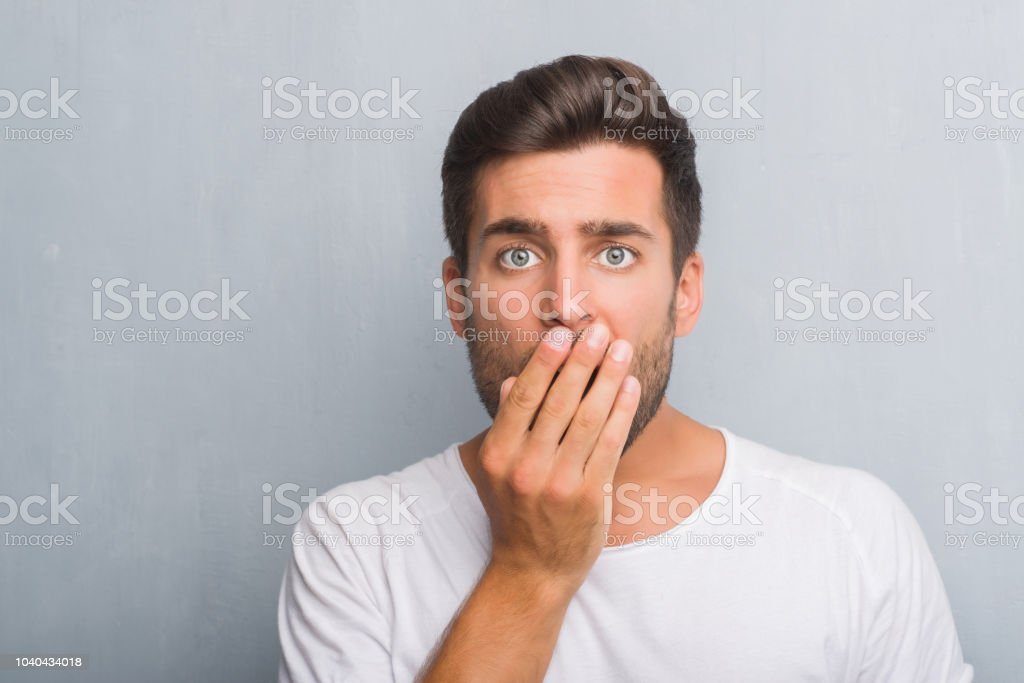 Handsome young man over grey grunge wall cover mouth with hand...