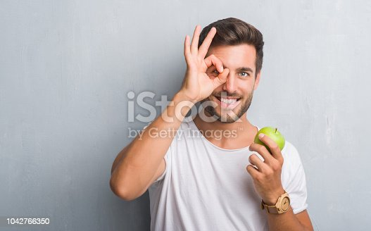 Handsome young man over grey grunge wall eating green apple with happy face smiling doing ok sign with hand on eye looking through fingers