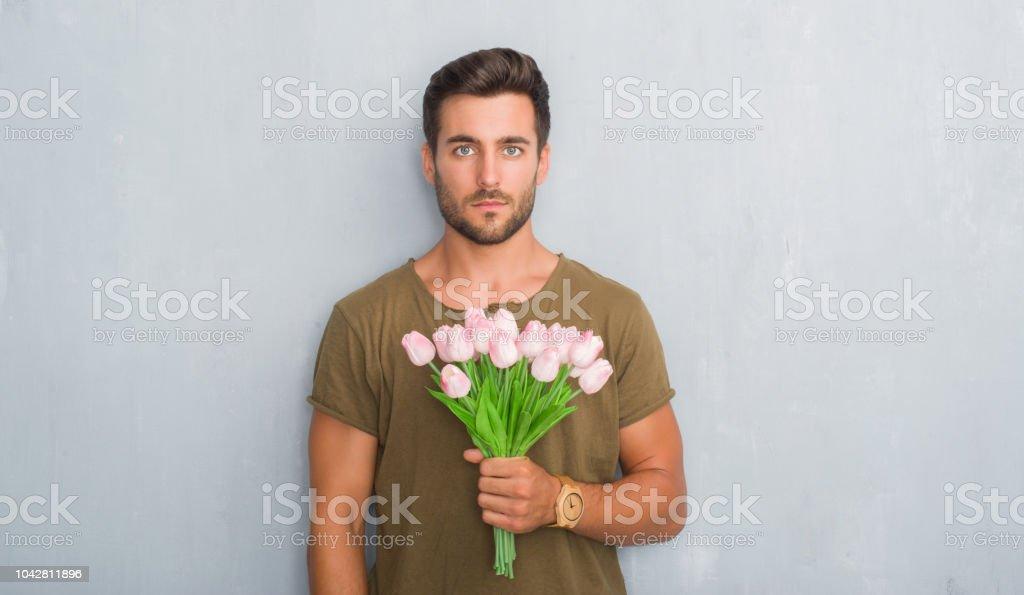 Çiçek buketi kendine güvenen bir ifade ile acımak yüz ciddi düşünüyorum tutarak gri grunge duvarın üzerinden yakışıklı genç stok fotoğrafı