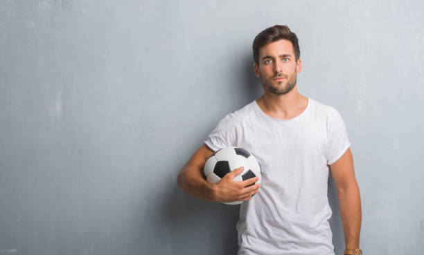 handsome young man over grey grunge wall holding soccer football ball with a confident expression on smart face thinking serious - soccer supporter portrait imagens e fotografias de stock