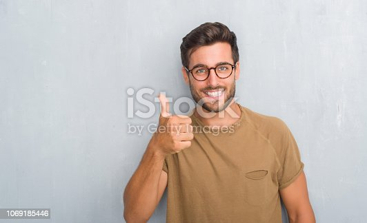 istock Handsome young man over grey grunge wall wearing glasses doing happy thumbs up gesture with hand. Approving expression looking at the camera with showing success. 1069185446