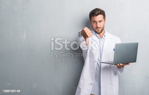 Handsome young man over grey grunge wall wearing white coat using laptop with angry face, negative sign showing dislike with thumbs down, rejection concept
