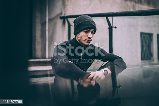 Young, handsome man in black outfit, wearing hat, sitting on wooden stairs.