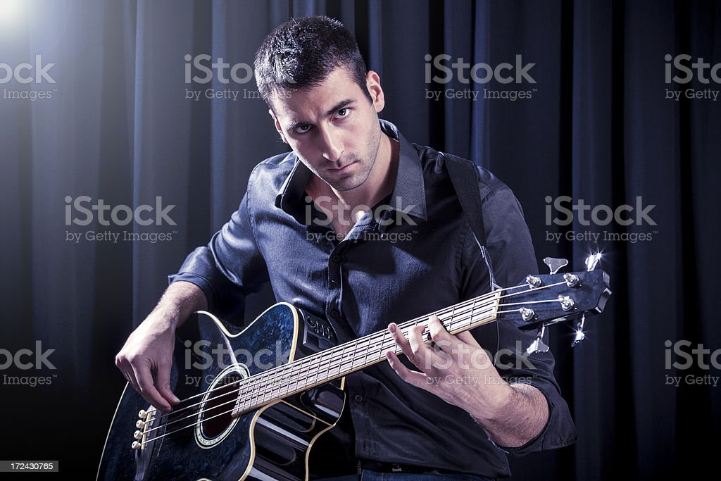 Handsome young man playing acoustic guitar on a stage royalty-free stock photo