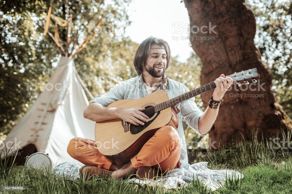 Jovem bonito tocando guitarra perto da tenda - foto de acervo