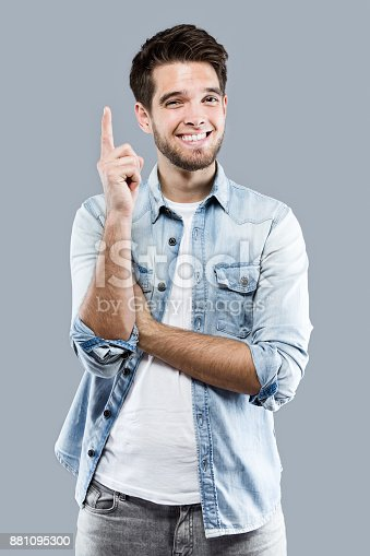istock Handsome young man pointing up over gray background. 881095300