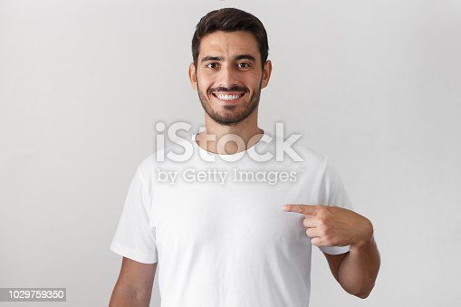 istock Handsome young man pointing with index finger at blank white t-shirt with empty space for your advertising text or image, standing isolated on gray background 1029759350