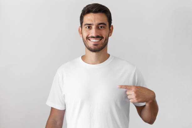 Handsome young man pointing with index finger at blank white t-shirt with empty space for your advertising text or image, standing isolated on gray background stock photo