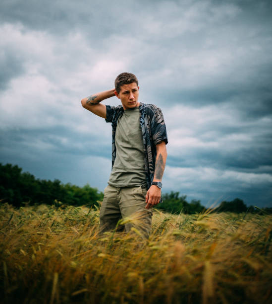 Handsome young man posing on the wheat field