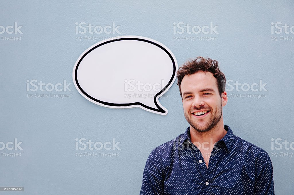 Handsome young man posing with speech bubble stock photo