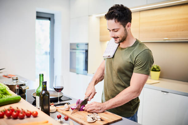 Handsome young man preparing helathy dinner, standing in the kichen and cutting vegetables stock photo