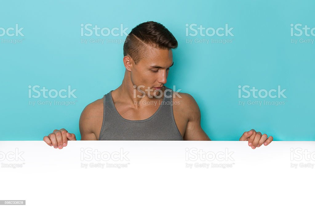 Handsome Young Man Reading Placard foto royalty-free