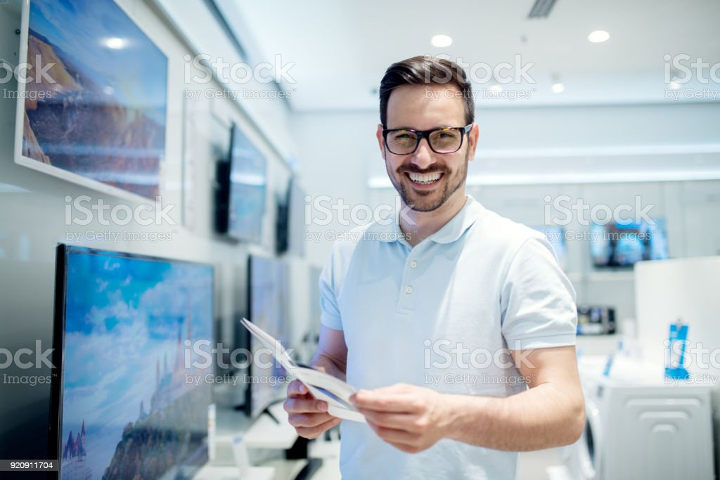 Handsome young man reading the use instructions. Buying new tv set at the tech store. stock photo
