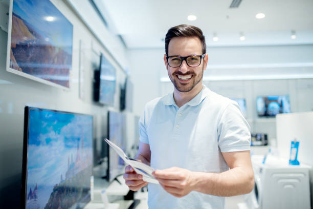 handsome young man reading the use instructions. buying new tv set at the tech store. - happy person buy appliances stock photos and pictures