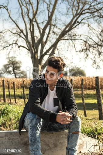 1094815168 istock photo Handsome young man rests in an agricultural area with a background of cultivation of corn. Cordoba Argentina. 1217457440