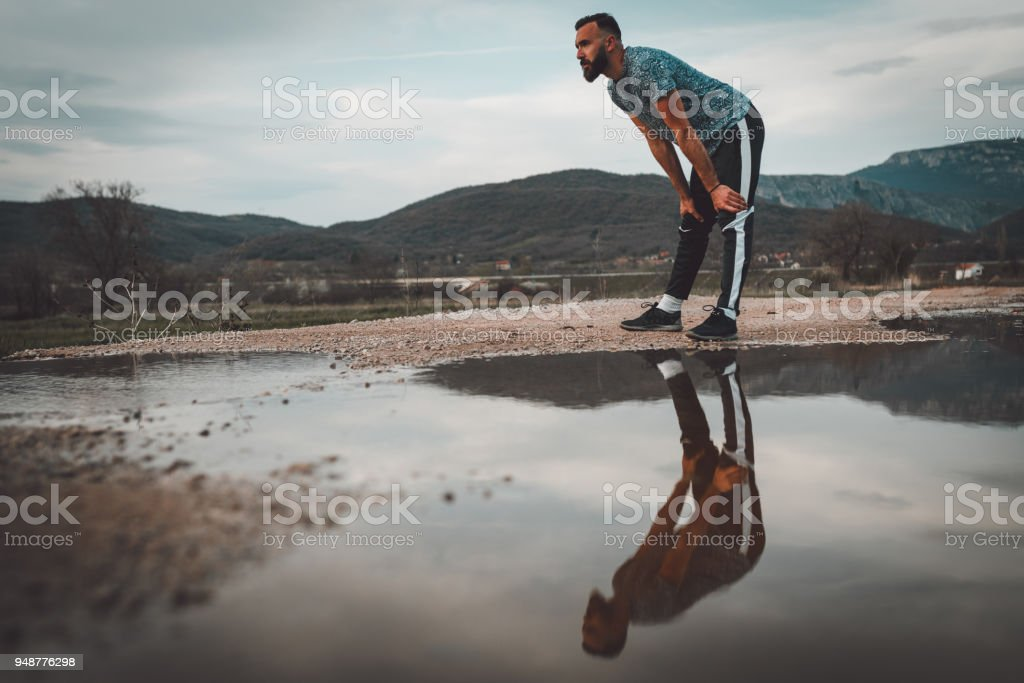 Handsome young man running outdoors stock photo