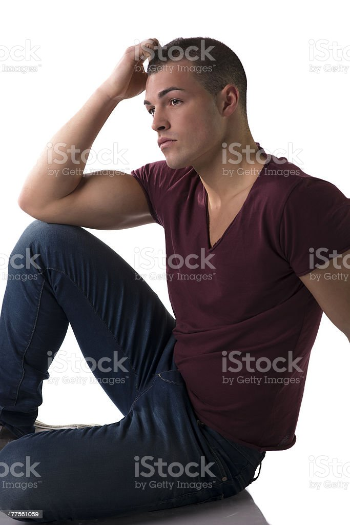 Handsome young man sitting, hand touching his head royalty-free stock photo