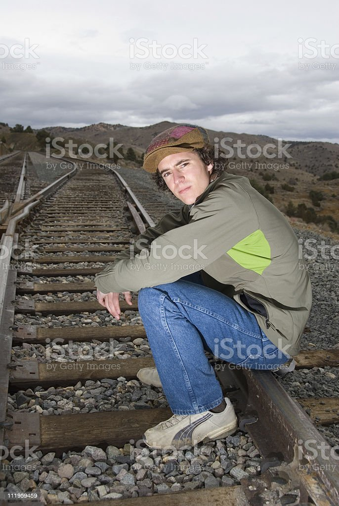 Handsome young man sitting on the railroad tracks stock photo