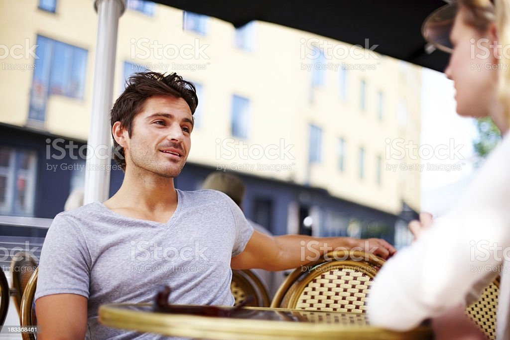 Handsome young man sitting with his girlfriend at a cafe royalty-free stock photo