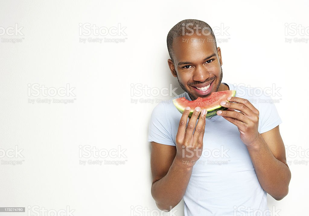 Handsome young man smiling and eating fresh watermelon stock photo