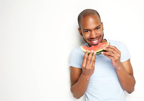 atractivo joven sonriente comiendo sandía fresca y - negras maduras fotografías e imágenes de stock