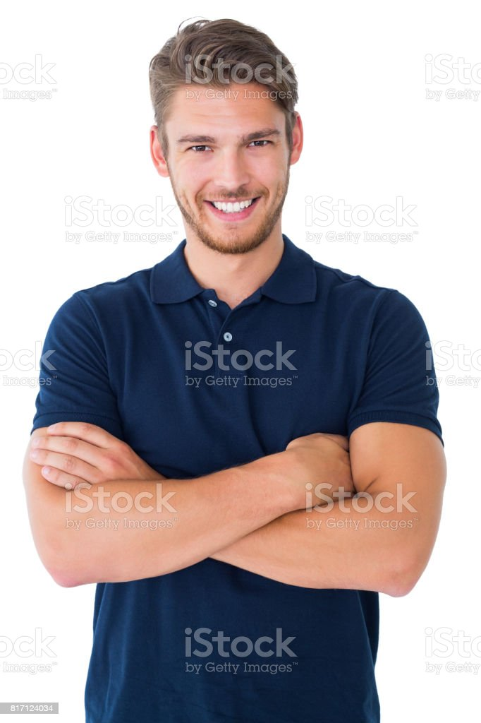 Handsome young man smiling with arms crossed stock photo