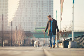 Handsome young man spending time with his dog walking outdoors in the city