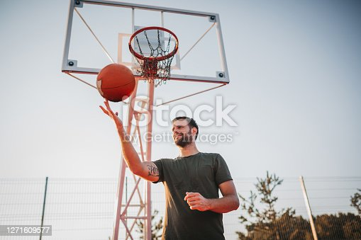 Handsome Young Man Spinning Basketball On Finger