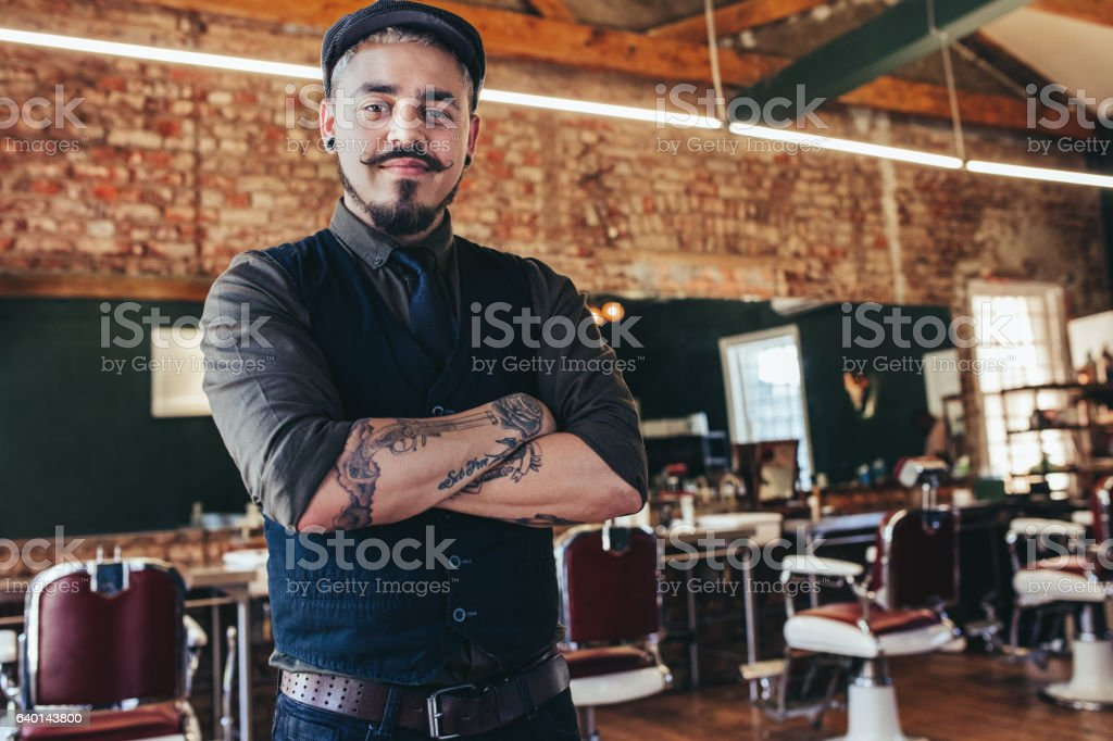 Handsome young man standing at barber shop stock photo