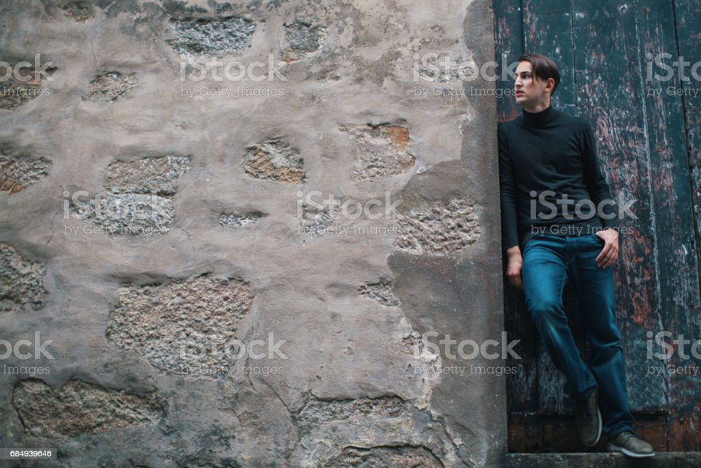 Handsome young man standing near old stone wall. Picture with space for text. Lizenzfreies stock-foto