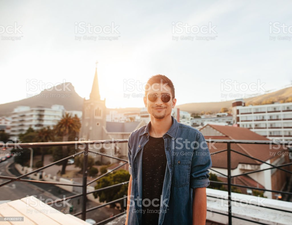 Handsome young man standing on the rooftop stock photo