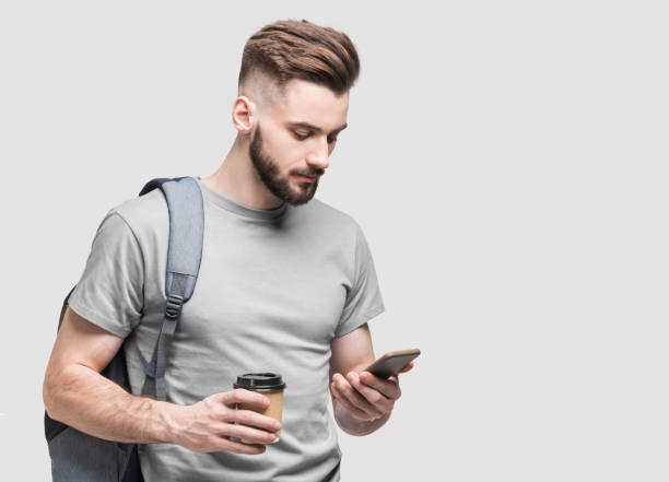 Handsome young man student using smartphone stock photo