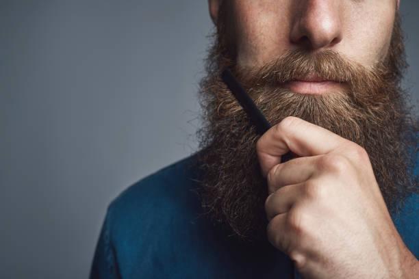 beau jeune homme style sa barbe avec un peigne - peigne photos et images de collection