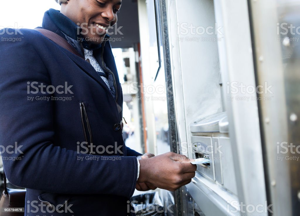 Handsome young man taking cash from ATM with credit card. stock photo