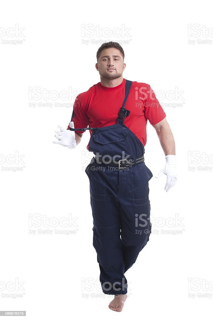Handsome young man taking off his overalls stock photo