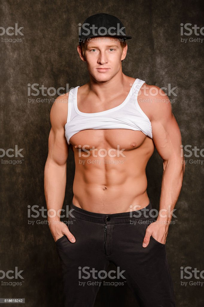 Handsome young man taking off white t-shirt stock photo