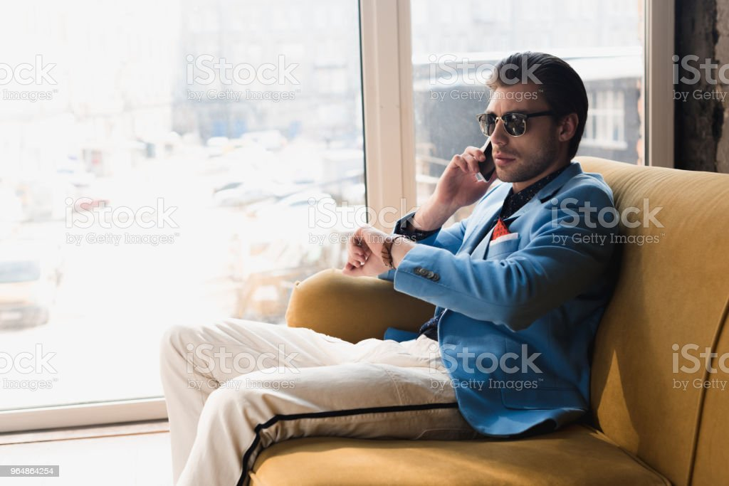 handsome young man talking by phone while sitting on couch and looking at watch royalty-free stock photo