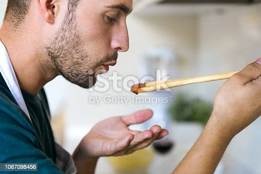 Close up of handsome young man tasting the fried with wooden spoon in the kitchen at home.