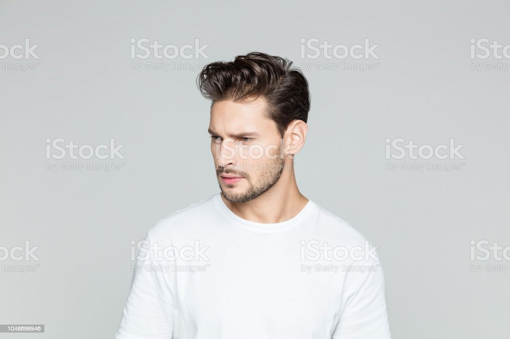 Handsome young man thinking Portrait of handsome young man with beard looking away thinking on grey background. 25-29 Years Stock Photo