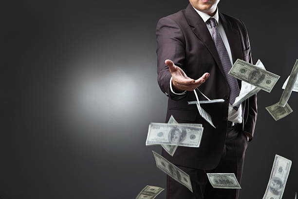 handsome young man throwing money - throw money away stock pictures, royalty-free photos & images